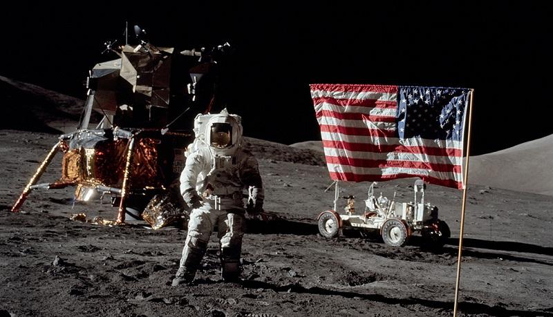 Se observa un astronauta junto a la bandera de Estados Unidos