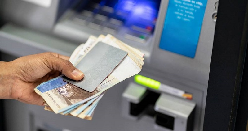 Unrecognizable man holding his debit card and cash after withdrawing from atm - Crad to edit