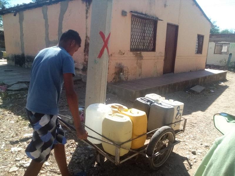En carretillas cargan las canecas de agua.   FOTO/CORTESÍA.